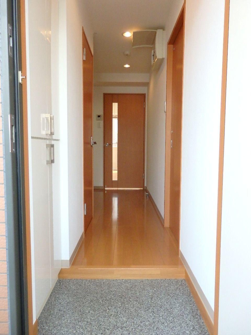 玄関を開けると人感センサーでライトが点灯し、明るい木目調のフローリングが居室へと延びています。